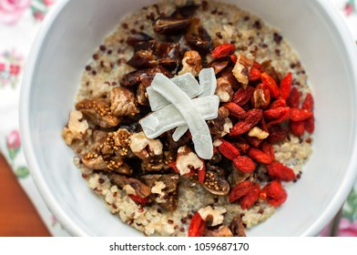 Healthy breakfast bowl. Milky quinoa porridge with goji, coconut, figs and nuts. Cup of cappuchino coffee. Selective focus, closeup view
