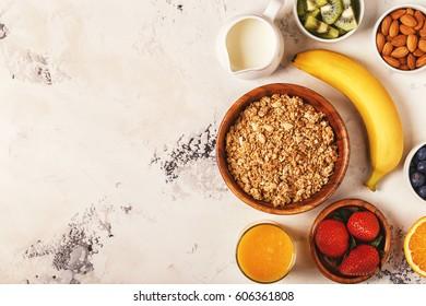 Healthy breakfast - bowl of muesli, berries and fruit, nuts, orange juice, milk, top view.