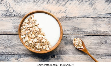 Healthy breakfast. Bowl of muesli with natural yogurt on wooden table. Top view.  Wide format.