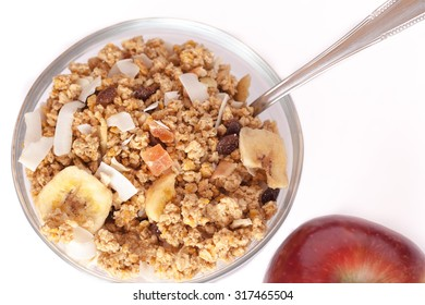 A healthy breakfast with a bowl of muesli and tasty red apple