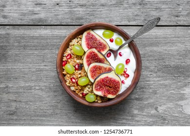 healthy breakfast. bowl of oat granola with yogurt, pomegranate seeds, figs, grape and nuts on rustic wooden table. top view. flat lay