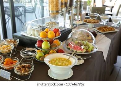 Healthy breakfast buffet table of fruit salad, various fruits, dried fruits, yoghurts during summer vacation in greek hotel.