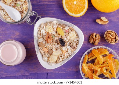 Healthy breakfast. Ceramic bowl with oat flakes, dried fruits, nuts on a violet wooden background
