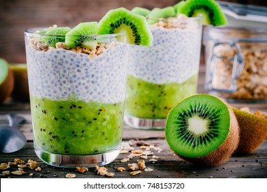 Healthy breakfast. chia pudding with kiwi and granola in glass on wooden background