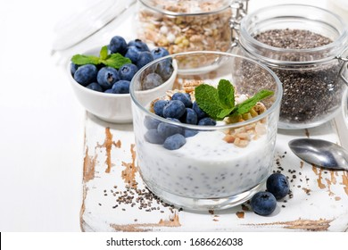 healthy breakfast with chia-pudding and fresh blueberries on white board, closeup