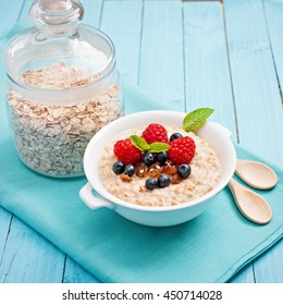 Healthy breakfast for children - oatmeal porridge with fresh berries on blue wooden background, health and diet concept