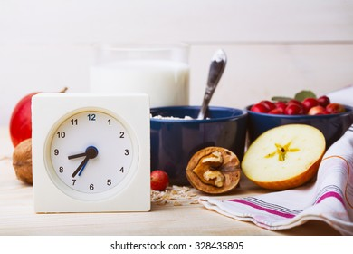 healthy breakfast - clock, milk, oatmeal, cranberries, nuts, apples on a wooden table
