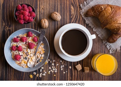 Healthy breakfast with coffee, fruit, cereals, juice on dark wooden table