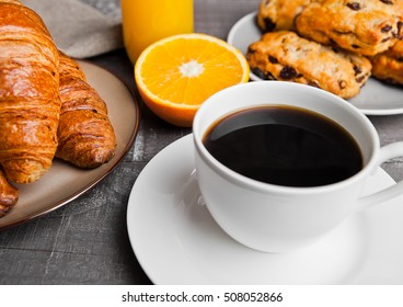 Healthy breakfast with coffee juice fruits pastry on wooden table