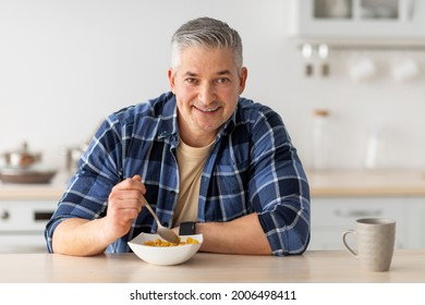 Healthy breakfast concept. Cheerful senior man having breakfast, eating cereals and drinking coffee, sitting in kitchen interior and enjoying morning time on weekend, free space