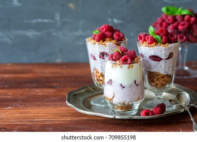 Healthy breakfast concept. Granola parfait with yougurt and chia seeds and raspberries, space for text