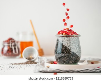 Healthy breakfast concept and idea - two colors chia pudding with organic raw pomegranate. Glass jar with black charcoal and white vegan milk chia pudding with falling pomegranate. Copy space