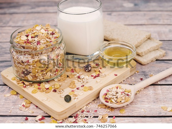 Healthy breakfast concept with muesli, milk and honey on a wooden background