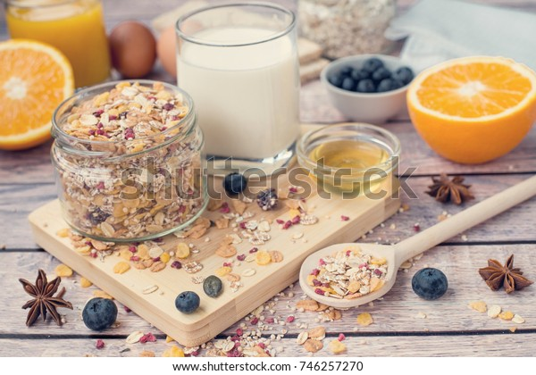 Healthy breakfast concept with muesli, milk, orange, blueberries and honey on a wooden background