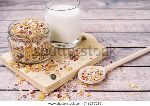 Healthy breakfast concept with muesli and milk  on a wooden background