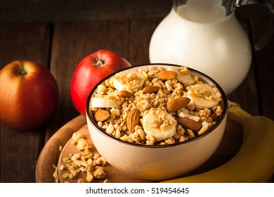 Healthy breakfast concept with oat flakes and fresh apples on wooden rustic background. Food made of granola and musli. Healthy banana smoothie with muesli, honey and milk. Breakfast with muslie.