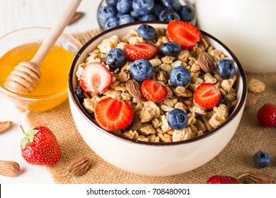 Healthy breakfast concept with oat flakes and fresh berries on rustic background. Food made of granola, muesli. Healthy banana smoothie with blackberries, muslie, strawberries, blueberries and honey.