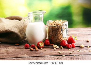 Healthy breakfast concept with oat flakes and fresh berries on rustic background. Food made of granola and musli. Healthy muesli with strawberries, nuts and milk.