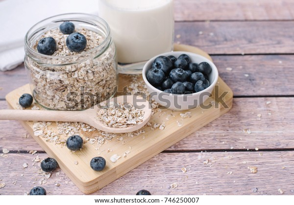 Healthy breakfast concept with oatmeal, glass of milk and blueberries on a wooden background