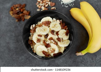 Healthy breakfast concept with oatmeal porridge with bananas,  nuts, raisins, sesame seeds  Top view. Super food. Food made of granola and musli.