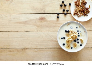 Healthy breakfast concept with oatmeal porridge with bananas, milk, blueberries,  nuts, raisins, chia seeds and currants. Top view. Super food