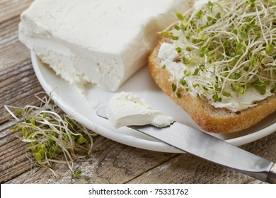 healthy breakfast concept - a roll with cream cheese and broccoli sprouts