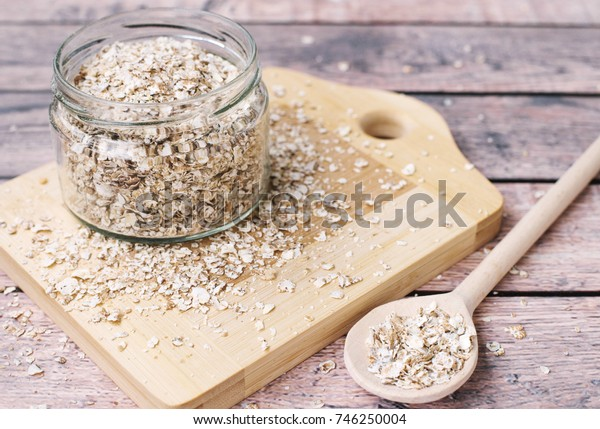 Healthy breakfast concept with uncooked oatmeal on a wooden background