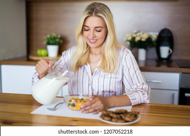 healthy breakfast concept - woman in pajamas eating corn flakes with milk in modern kitchen