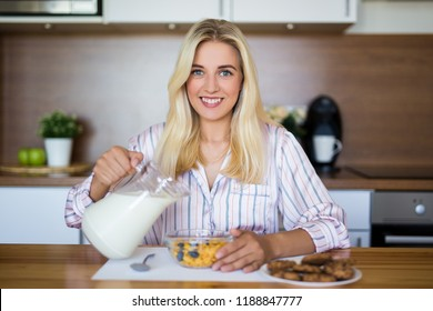 healthy breakfast concept - young beautiful woman pouring milk in bowl with corn flakes in modern kitchen