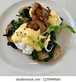 A healthy breakfast consisting of poached eggs, toasts, hollandaise and bacon taken from above