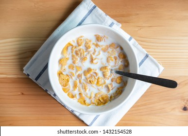 Healthy breakfast with corn flakes and milk on wooden table, Top view