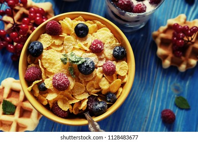 Healthy breakfast. Corn flakes with raspberries and blueberries, granola with yogurt and berries, wafers and milk. A great start to the day. Top view.