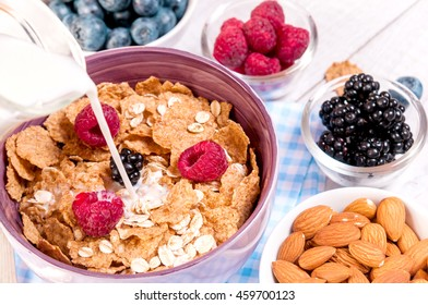 healthy breakfast with cornflakes berries, milk and almond nuts on wooden table