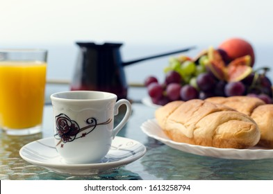 Healthy breakfast with a cup of coffee and plate of delicate and lush croissant in the foreground, Turkish coffeepot, glass of orange juice, plate of grapes on the table in the background. Copy space.