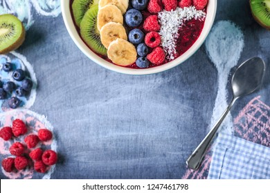 Healthy breakfast with delicious acai smoothie in bowl on chalk board