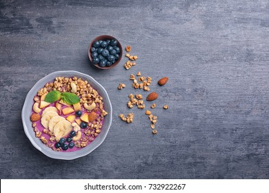 Healthy breakfast with delicious acai smoothie in plate on table