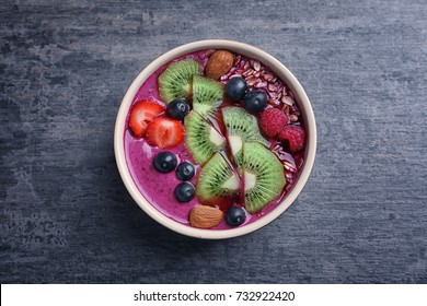 Healthy breakfast with delicious acai smoothie in bowl on table