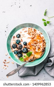 Healthy breakfast or dessert. Yoghurt with oat flakes, blueberries, apples and honey in pastel blue bowl on grey stone background. Captured from above (top view, flat lay). Free copy (text) space.