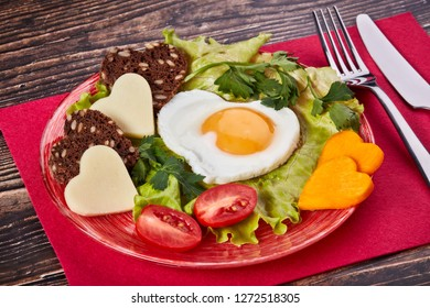 Healthy breakfast. Dish with fried egg, bread, cheese and vegetables in the shape of a heart on a wooden background. Top view.