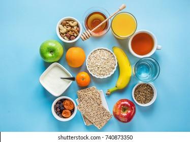 Healthy Breakfast Fiber Sources Digestion Oatmeal Honey Fruits Apples Banana Orange Juice Water Green Tea Nuts. Light Blue Tabletop. Modern Funky Flat Lay Top View. Creative Food