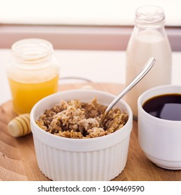 healthy breakfast fresh cereal, milk bottle, coffee cup and honey jar, toned warm sunny morning light