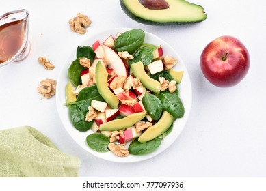 Healthy breakfast with fresh fruit salad from apples, avocado, spinach and nuts on light background. Top view, flat lay