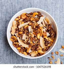 Healthy breakfast. Fresh granola, muesli with coconut, banana and nuts in a white bowl on grey textile background. Top view.