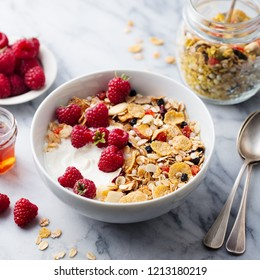 Healthy breakfast. Fresh granola, muesli with yogurt and berries on marble background. Close up.