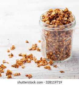 Healthy breakfast. Fresh granola, muesli in a glass jar. copy space.Organic oat,almond and sunflower seeds