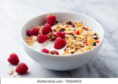 Healthy breakfast. Fresh granola, muesli with yogurt and berries on marble background.