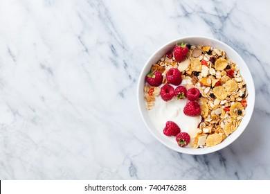 Healthy breakfast. Fresh granola, muesli with yogurt and berries on marble background. Top view. Copy space.