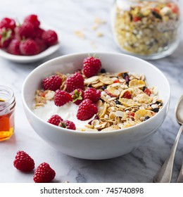 Healthy breakfast. Fresh granola, muesli with yogurt and berries on marble background.