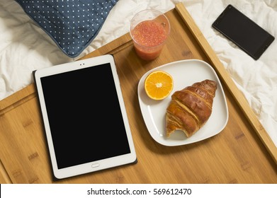 Healthy breakfast of fresh, orange and croissant at bed with tablet and mobile phone. Empty screen