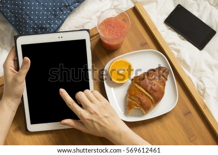 Healthy breakfast of fresh, orange, croissant and mobile phone at bed. Woman hands holding tablet. Empty screen.